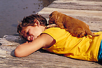 Young Boy relaxing on pier with puppy on his back, animals, child, children. Hawaii.