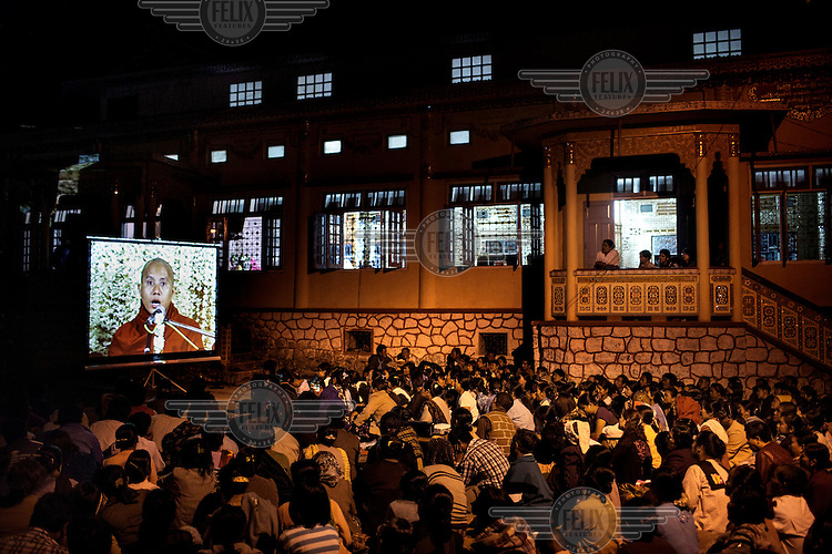 Followers of U Wirathu, the spiritual leader of the radical Buddhist 969 movement, watch him deliver a sermon on a projector screen in the overflow area of the Thein Taung Monastery in Taunggyi, Shan State. /Felix Features