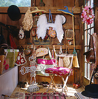 Edie's dressing room is a riot of bags and personal items which hang from every available hook on the rustic planking of the wall
