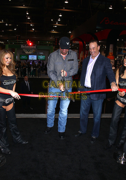 Toby Keith, Jon Taffer, Wild Shot Mezcal girls.Superstar Toby Keith and Jon Taffer conduct the ribbon cutting ceremony for the 27th Annual Nightclub & Bar Convention and Trade Show at the Las Vegas Convention Center, Las Vegas, Nevada, USA..March 13th, 2012.full length grey gray shirt sunglasses shades black baseball cap hat jeans denim  ribbon giant oversized scissors cut cutting .CAP/ADM/MJT.© MJT/AdMedia/Capital Pictures.