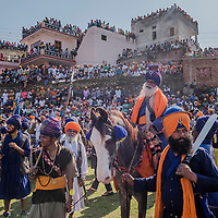 ANANDPUR SAHIB, INDIA - March 06, 2015: Nihangs, or &quot;Sikh warriors&quot; arrive to participate in a horse riding competition during Hola Mohalla celebrations on March 06, 2015 in Anandpur Sahib, India. Hola Mahalla or simply Hola is a Sikh event, which takes place on the first of the lunar month of Chet, which usually falls in March, and sometimes coincides with the Sikh New Year. It was started by Guru Gobind Singh the tenth Sikh guru in 1701 AD. Hola Mohalla is a three day Sikh festival, in which Nihang Sikh 'warriors' perform Gatka (mock encounters with real weapons), tent pegging and bareback horse-riding.<br /> Daniel Berehulak for The New York Times