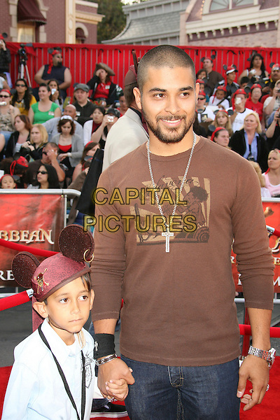"CHRISTIAN & WILMER VALDERRAMA.""Pirates Of The Caribbean: At World's End"" World Premiere held at Disneyland, Anaheim, California, USA,.May 19th, 007.3 half length brown top holding hands brothers siblings family hat beard facial hair .CAP/ADM/RE.©Russ Elliot/AdMedia/Capital Pictures"