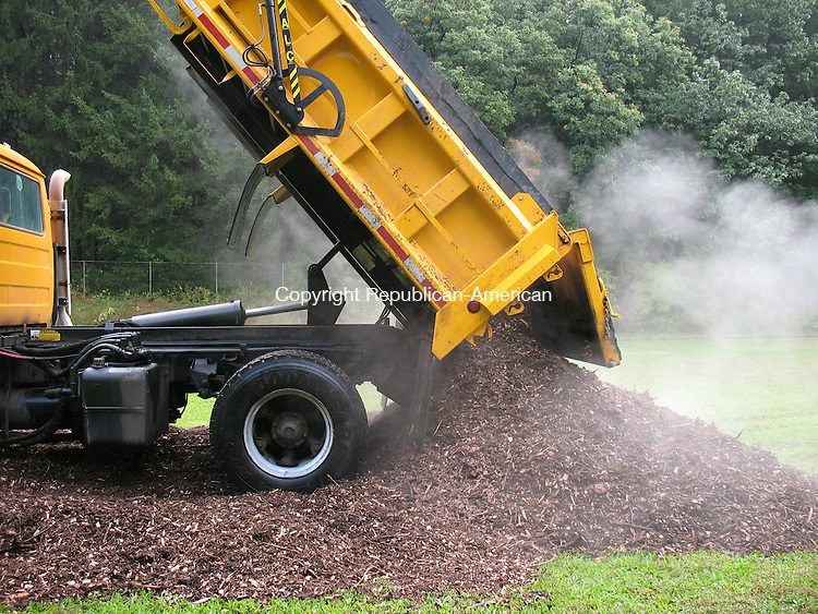 WATERBURY, CT - One of numerous truckloads of mulch, donated by Watertown, is dumped on the bowling green at Fulton Park on Wednesday for Brass City Harvest's largest endeavor to create a community garden in Waterbury.