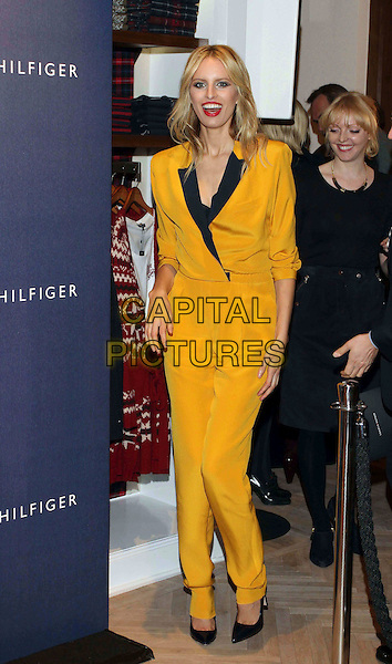 Karolina Kurkova.Tommy Hilfiger Store Opening Cocktail party, Hamburg, Germany..November 16th, 2011.full length black yellow playsuit mouth open smiling red lipstick .CAP/PPG.©People Picture/Capital Pictures