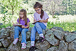 Two girls sitting on a stone wall studying.