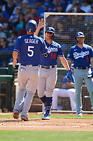 Enrique Hernandez (14) of the Los Angeles Dodgers congratulates teammate Corey Seager (5) after scoring a run during a Cactus League Spring Training game against the Los Angeles Dodgers on March 8, 2020 at Surprise Stadium in Surprise, Arizona. Rangers defeated the Dodgers 9-8. (Tracy Proffitt/Four Seam Images)