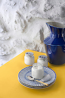 A blue jug and blue and white plates strike the perfect colour balance on the yellow kitchen table