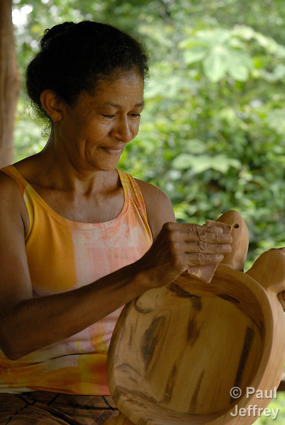 Edna Machin da Silva sands a hardwood turtle bowl crafted by members of the Esperança Sustainable Development Project, a pioneering jungle community where U.S. Catholic Sister Dorothy Stang worked. Stang was murdered here for her defense of the jungle and landless poor families like this one which survive there. The Project's families use the forest in a sustainable way.