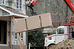 A specialized crane moves tons of gypsum wallboard in the background.  Work can't finish fast enough on constructing 'teardown' houses in Atlanta's depressed housing market.