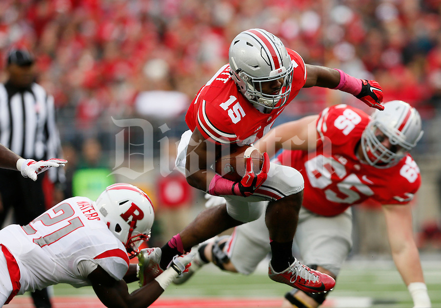 Ohio State Buckeyes running back Ezekiel Elliott (15) leaps away from Rutgers Scarlet Knights defensive back Lorenzo Waters (21) with coverage by Ohio State Buckeyes offensive lineman Pat Elflein (65) during Saturday's NCAA Division I football game against the Rutgers Scarlet Knights at Ohio Stadium in Columbus. The Buckeyes led at halftime 35-7. (Dispatch Photo by Barbara J. Perenic)
