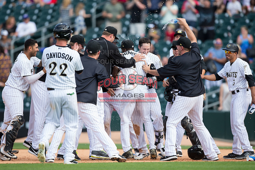 Jason Coats (17) of the Charlotte Knights is mobbed by his teammates after his walk-off single against the Gwinnett Braves in the bottom of the 11th inning at BB&T BallPark on May 22, 2016 in Charlotte, North Carolina.  The Knights defeated the Braves 9-8 in 11 innings.  (Brian Westerholt/Four Seam Images)