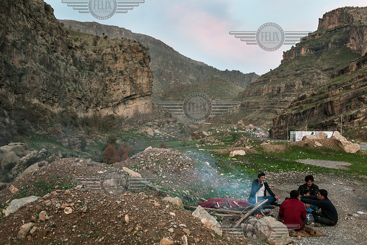 A group of men picnic in the evening near the town of Khalifa in the Kurdish northern part of Iraq.
