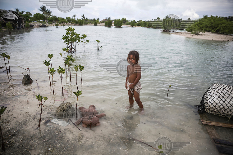 Tietaake, three, standing near her teddy-bear floating in a flooded area of Eita village. During high tides many villages in South Tarawa become inundated by sea water.