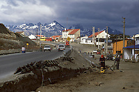 City crews in Ushuaia, Argentina, prepare to pave a dirt track in an fast-growing neighborhood. The peaks of the Sampaio range of Chile's nearby Hoste Island loom over the boom and bust development of Ushuaia, the growth of which was first fueled by an Argentine prison at the end of the 19th century, then by naval bases, free trade zones and now tourism.