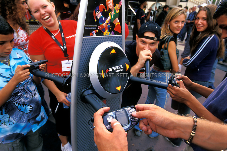 9/27/2003--Montpellier, France..MC Loran Coffinier rapping while a member of the public plays on Nokia's new N-gage. Nokia's 'N-gage Tour', promoting the company's new gaming platform, arrived in Montpellier, France, Saturday, September 27th as part of a European-wife tour. The show, featuring local hip hop artists as well as traveling MCs, is aimed to bring the new gaming platform to a younger audience. The Nokia N-Gage also features a phone, MP3 music player and bluetooth...All photographs ©2003 Stuart Isett.All rights reserved.This image may not be reproduced without expressed written permission from Stuart Isett.
