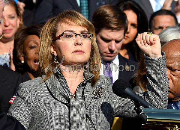 Former United States Representative Gabrielle Giffords (Democrat of Arizona) raises her fist during her remarks as US House Democrats appear on the East Steps of the US Capitol to make a statement against gun violence in the wake of the Las Vegas Massacre in Washington, DC on Wednesday, October 4, 2017. Photo Credit: Ron Sachs/CNP/AdMedia