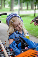 Unhappy Polish girl age 4 with soda wearing bicycle helmet after bike ride. Paderewski Park Rzeczyca Central Poland
