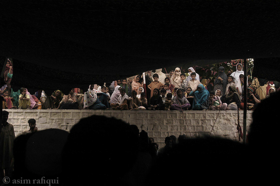 bari imam shrine, islamabad, pakistan 2004: women pilgrims with their children listen to a qawwali concert from a terrace<br />