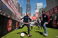 A young player takes a shot as former men's national team player Tab Ramos moves to defend during the centennial celebration of U. S. Soccer at Times Square in New York, NY, on April 04, 2013.