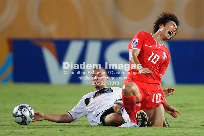 SUEZ, EGYPT - SEPTEMBER 29:  Florian Jungwirth of Germany (l) tackles Young Cheol Cho of the Korea Republic (r) during a FIFA U-20 World Cup soccer match  September 29, 2009 in Suez, Egypt.  (Photograph by Jonathan P. Larsen)