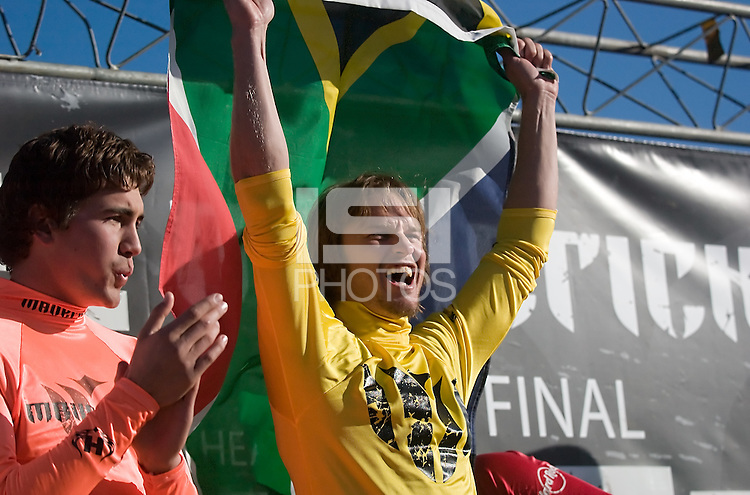 "Grant ""Twiggy"" Baker holds up a South African flag standing next to Greg Long on stage during the awards ceremony at the 2008 Mavericks Surf Contest in Half Moon Bay, Calif., Saturday, January 12, 2008...Photo by David Calvert/isiphotos.com"