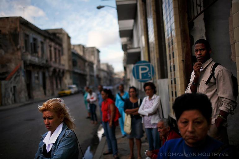 Cubans wait at a bus stop in central Havana, Cuba on 28 October 2008.
