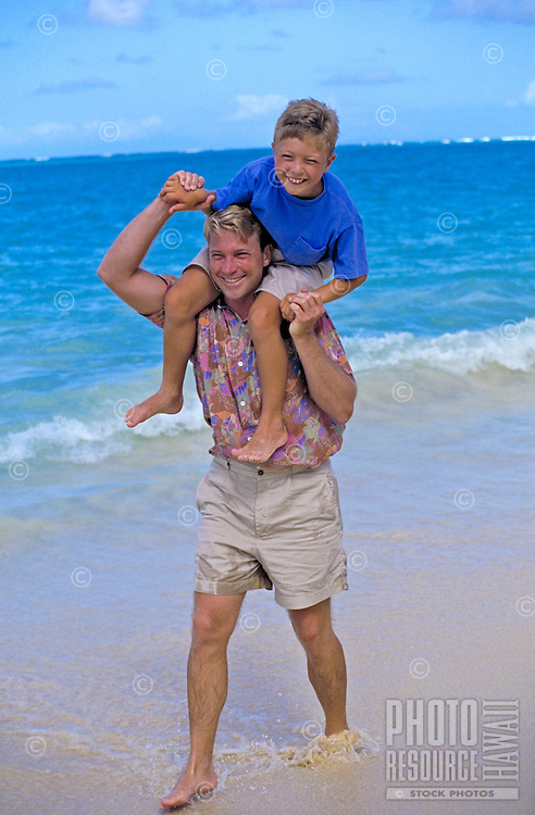 A father with his son perched on his shoulders have fun walking along the shore of a beautiful white sand beach on Oahu.