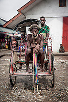 Hetuk Hilapo, 70, from Aikima village sits in a 'bechak' (cycle rickshaw) in Jibama marke. A few years ago Hetuk used to walk from his village to the market, but nowadays he uses cheap cycle rickshaws to make his way faster, paying only 5000 rupiahs (GBP 0.26) per ride.
