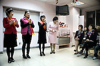 Women line up to discuss their feelings about Mary Kay makeup and beauty products at a Mary Kay meeting center in Nanjing, Jiangsu, China.