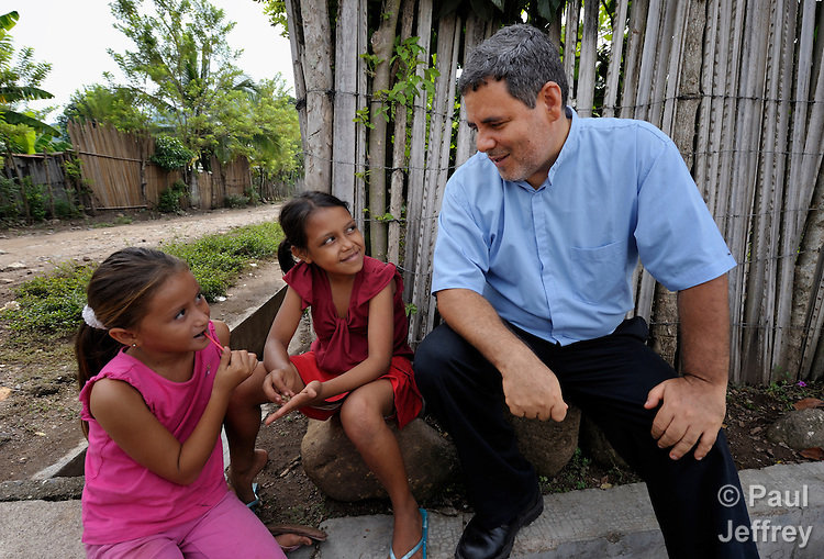 The Rev. Juan Guerrero, a native of Colombia, is a United Methodist missionary and superintendent of the church's mission in Honduras. Here he visits with children in the northern Honduran village of Ceibita.