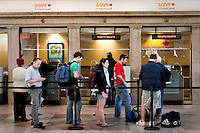 Travelers wait in line to buy a train ticket at a VIA Rail Canada booth in Toronto Union station April 20, 2010.