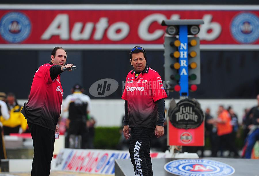 Nov. 10, 2011; Pomona, CA, USA; NHRA funny car driver Cruz Pedregon (right) with a crew member during qualifying at the Auto Club Finals at Auto Club Raceway at Pomona. Mandatory Credit: Mark J. Rebilas-.