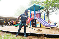 C.J. Blackmon, a senior biochemistry major from Pinson, Alabama, shovels gravel on the playgound at MSU's Child Development and Family Studies Center. Blackmon was one of over 600 MSU students volunteering throughout the community Monday as part of Service DAWGS Day.<br />