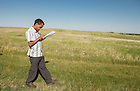 June 9, 2015; UNDERC West student Bereket Mamo, 21, from Augustana College, jots some notes in his workbook during a tour at Double Ditch Indian Village State Historic Sitealong the Missouri River north of Bismarck, North Dakota. (Photo by Barbara Johnston/University of Notre Dame)