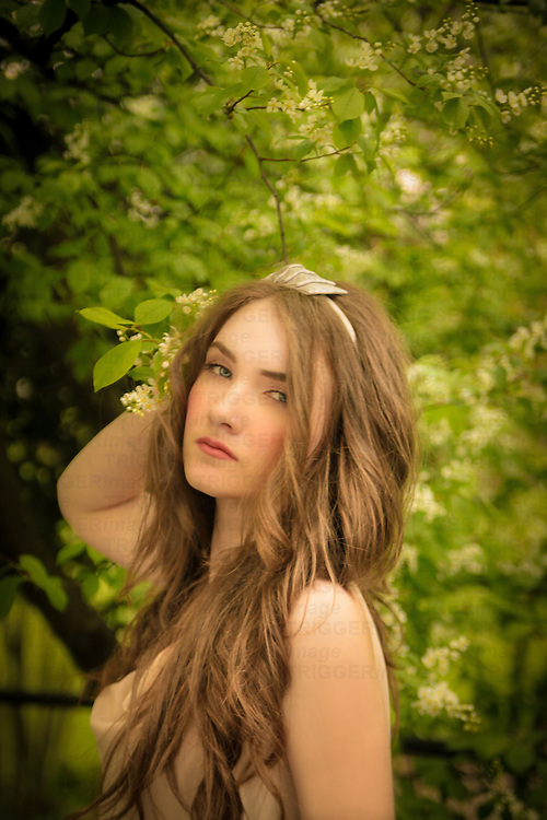 Young girl with blue eyes, pale skin and blond hair outdoors in spring looking at camera