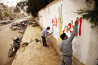 Syria, Deir az-Zor, 2013/03/23..Painters place a graffiti (Victory is coming) at a wall of the former college. They risking much as this road is knows as a sniper alley where Assad loyalist targeting bypassers..Syrie, Deir ez-Zor, 23/03/2013.Des artistes font un graffiti (la Victoire est à venir) sur la façade de l'ancien collège. Ils risquent leur vie car  cette rue, connue sous le nom de «sniper alley», est constamment sous le tir des snipers fidèles au régime d'al-Assad qui prenent les passants pour cible..Photo: Timo Vogt / Est&Ost Photography.