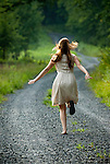 Young woman running up gravel country road