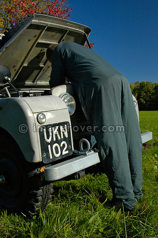 Mechanic checking the engine on a grey 1950's Land Rover Series One 86 inch Station Wagon. This Land Rover is in extremly original condition still with its original paint. Lovely autumn weather with beautiful coloured treas and blue sky. Dunsfold, UK, 2004. --- No releases available. Automotive trademarks are the property of the trademark holder, authorization may be needed for some uses.
