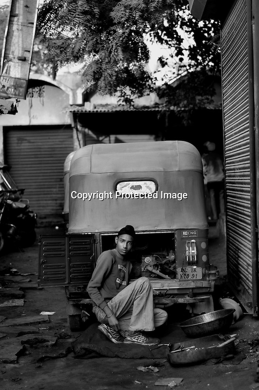 A Sikh child labour at Tilak Vihar. He works as a mechanic of three wheelers (auto rickshaw) in a road side garage. Tilak Vihar in New Delhi is called the widow colony. Widows and children of the Sikhs who were killed in 1984 Sikh Genocide live here. Four thousand Sikhs were killed in 72 hours in Delhi alone but no body till date has been punished for such an inhuman crime. Illiteracy, drug addiction, child labour and immense poverty characterize the area. Twenty five years ago all the male family members above the age of 15 were killed and burnt, leaving their uneducated widows and children behind to suffer, even after 25 years. The present generation is jobless, steeped in alcoholism and have lost their directions in life. November 2009. New Delhi, India, Arindam Mukherjee