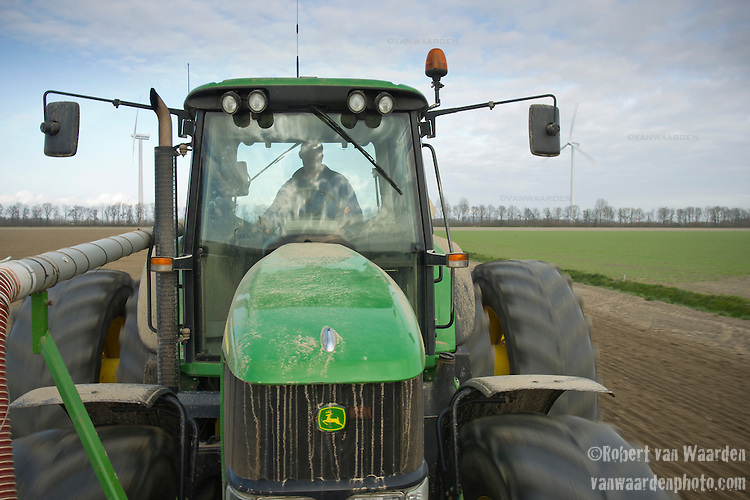 Ralph De Clerck prepares the field for potato planting on his farm in Swifterbant, the Netherlands. The de Clerck family has been farming wind energy for over a decade. Together the two brothers, Stephan and Ralph are producing over 8MW of wind energy and selling it to the grid. The wind energy is an important crop that allows them to diversify their product. They continue to farm their land, planting potatoes and the wind mills run in the background.