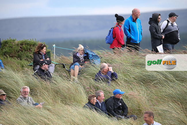 Spectators huddle in the long grass to stay out of the wind  during Round One of the 2016 Aberdeen Asset Management Scottish Open, played at Castle Stuart Golf Club, Inverness, Scotland. 07/07/2016. Picture: David Lloyd | Golffile.<br /> <br /> All photos usage must carry mandatory copyright credit (&copy; Golffile | David Lloyd)