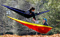 Clemson University senior Nicole Bryant, top, from Powdersville, and junior Meredith Alewine, from Anderson, relax in hammocks near the Strom Thurmond Institute on the school's campus on Thursday. The women said that they frequent the shady spot because it is close to most of their classes and more secluded and quiet than Bowman Field.