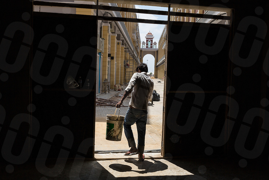 March 30, 2014 - Phnom Penh, Cambodia. A constuction worker walks out of a new building on Koh Pich island. The development called La Seine is intended as a replica of the French Riviera . © Nicolas Axelrod / Ruom