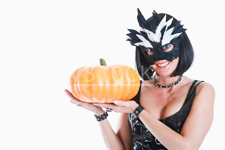 Studio portrait of woman wearing mask and holding pumpkin