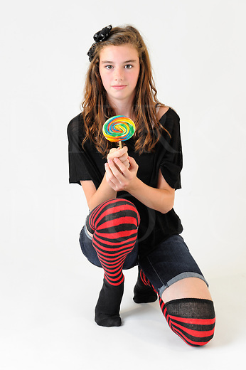 Girl holding lollipop while kneeling on bent knee, thirteen year old trendy American teenager wearing cutoff shorts and striped knee socks.