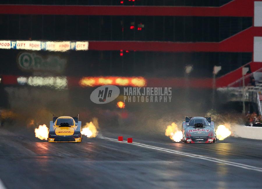 Jun 20, 2015; Bristol, TN, USA; NHRA funny car driver Del Worsham (left) races alongside Matt Hagan during qualifying for the Thunder Valley Nationals at Bristol Dragway. Mandatory Credit: Mark J. Rebilas-