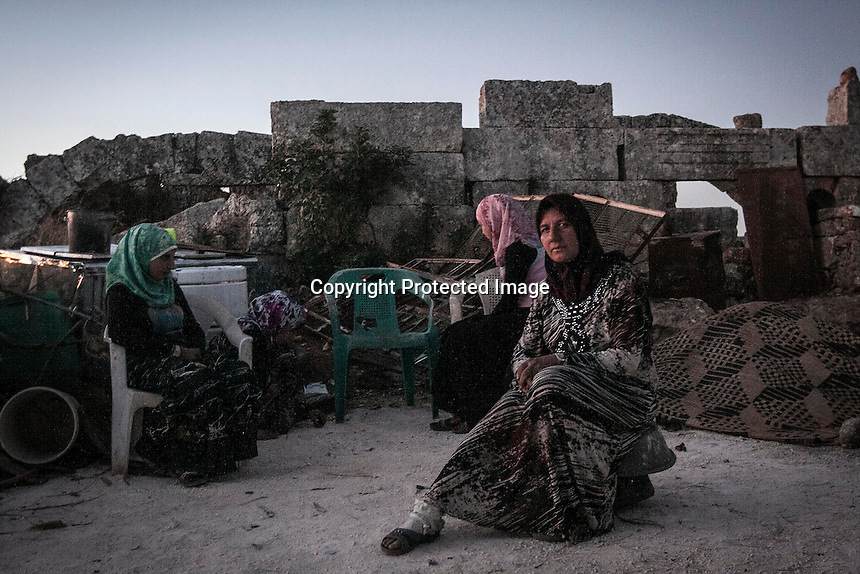 "In this Thursday, Sep. 26, 2013 photo, Syrian displaced women sit in the sunset at the Kafr Ruma, an ancient roman ruins used as temporary shelter by those families who have fled from the heavy fighting and shelling in the Idlib province countryside of Syria. Dozens of families settled in the ancient ruins known as ""The Forgotten City"" and declared human heritage by UNESCO, when the clashes between opposition fighters and government forces broke out in the region since more than two years ago. (AP Photo)"