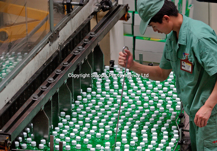 A man works on the soft drink bottling line at the Wahaha Beverage Manufacturing Base in Hangzhou, China. The privately owned Wahaha group is the largest beverage manufacturer in China with a total production of 3.75 million tons in assorted beverages last year. The group has recently decided to ship nearly 15 thousand cases of its Future Cola to the U.S..07-JUN-04