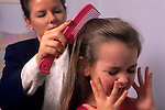 Early morning before school mother combing daughters hair ( 6 years old) with girl in pain Marysville Washington State USA MR