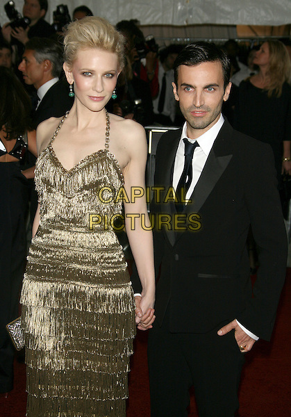"CATE BLANCHETT & NICOLAS GHESQUIERE.2007 Metropolitan Museum of Art Costume Institute Gala celebrating ""Poiret: King of Fashion"" exibition at the Metropolitan Museum of Art, New York City, New York, USA. .May 7th, 2007.half 3/4 length gold halterneck metallic dress clutch purse skinny tassels black suit holding hands .CAP/LNC/TOM.©TOM/LNC/Capital Pictures"